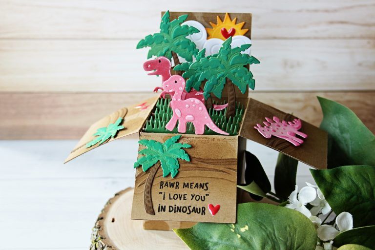 Die D-Lites Inspiration | Dinosaur Pop Up Card. Video tutorial by Nichol Spohr for Spellbinders using S2-273 Sun and Clouds, S3-317 Dinosaurs, S3-320 Picket Fence, S3-249 Palm Trees, S4-788 Classic A2 Waves Borders, S5-233 Heart & Home Scalloped Pop Up Box #spellbinders #popupbox #diecutting handmadecard #popupcard